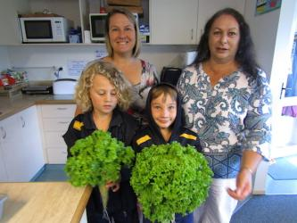Students show lettuces to their teachers