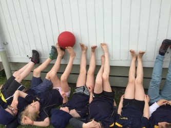 We are cooperatively passing the ball along the wall with our feet